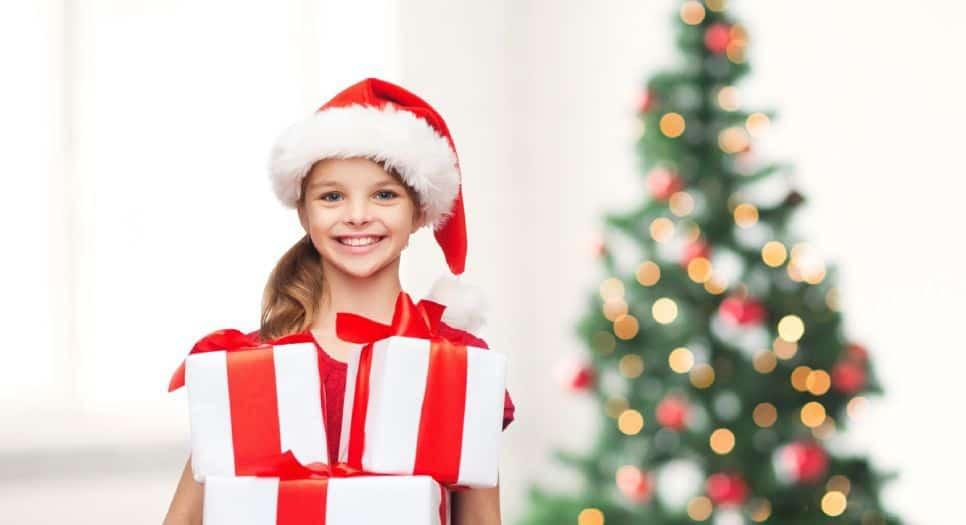 Foto di una bambina felice con regali di Natale